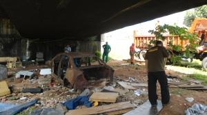 Supervisor Geral de Fiscalização Ambiental observa veículo que foi incendiado embaixo do viaduto